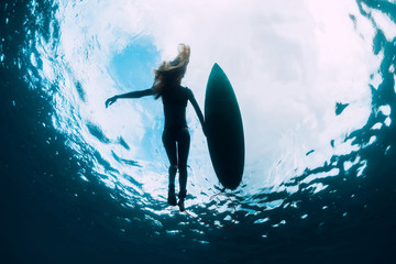 Surfer woman swim with surfboard. Surf girl in sea.