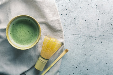Top view of green tea matcha in a bowl on concrete surface with copy space