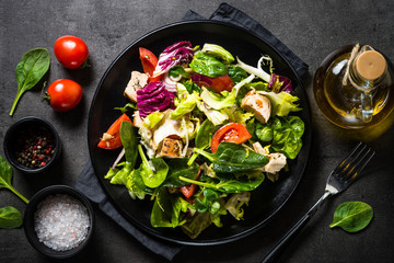 Green salad with chicken and vegetables on black.