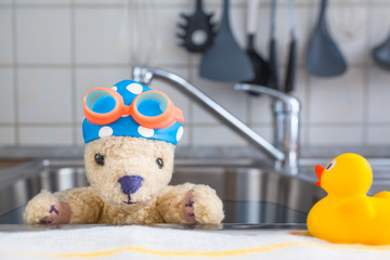 Home Swimming Lesson / Kitchen stainless steel sink as swimming pool, cute toy teddy bear inside wear blue white dotted bathing cap and swim goggles, rubber duck as teacher outside (copy space)