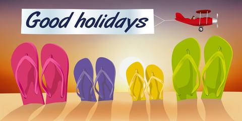 Concept des vacances à la plage, avec des tongs plantées dans le sable et un avion qui passe devant un coucher de soleil en tirant une banderole sur laquelle est écrit bonnes vacances.