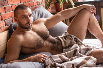 Young muscular male model lying in bed with blanket