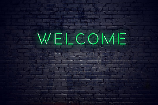 Brick wall at night with neon sign welcome