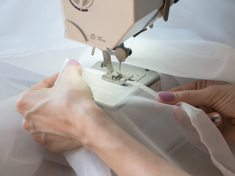 Hand sews a tulle on the sewing machine.