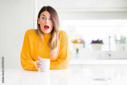 Young beautiful woman drinking a cup of coffee at home