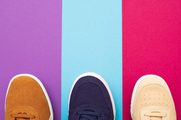 Three pair of sneakers on colored background