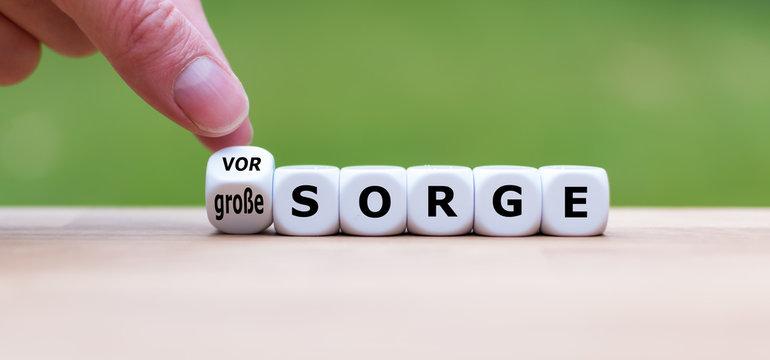 """Hand dreht einen Würfel und ändert den Ausdruck """"große Sorge"""" in """"Vorsorge""""."""