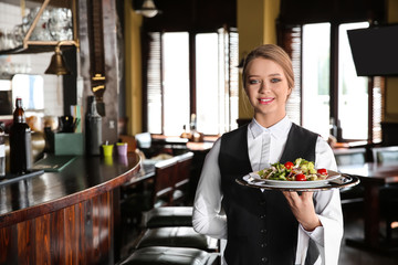 Young female waiter with salad in restaurant