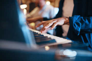 Musician playing keyboards during a recording studio session