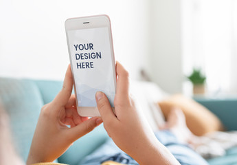 Person Using Mobile Phone on Couch Mockup