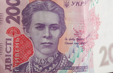 Ukrainian money. Banknote of Ukrainian hryvnia. Background of two hundred hryvnia banknotes, coins in piles, close-up