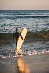 Young surfer with his white and yellow surfboard about to catch some waves