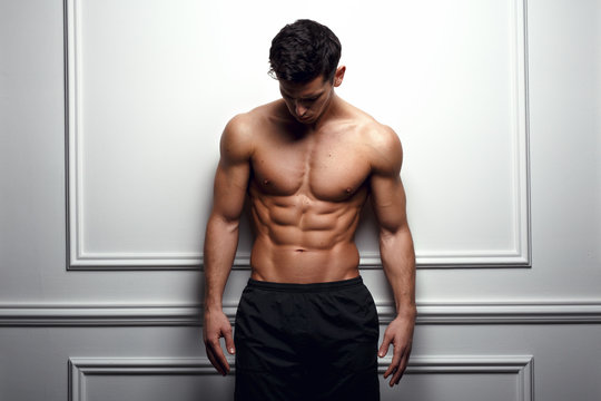 Athlete, muscular man at the white wall poses shirtless, showing six pack abs, white background.