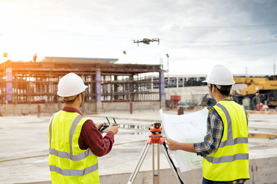 Engineer surveyor working with theodolite at construction site
