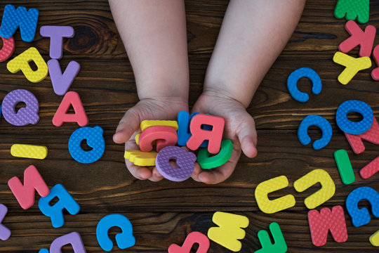 letters of the English alphabet in his hands on a wooden background. education. game.