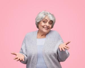 Smiling senior lady shrugging shoulders