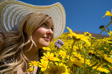 Beautiful blond woman wearing white straw hat in a yellow wildflower field, looking up at a blue sky in spring. Taken at Carrizo Plain National Monument during the California superbloom