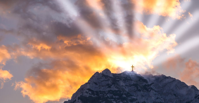 Silhouette of a cross on the top of a mountain with sun rays and dramatic clouds in the background. Symbol of God, religion, resurrection,miracle and faith.