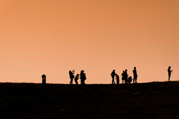 Silhouettes of hikers with backpacks enjoying sunset view from top of a mountain
