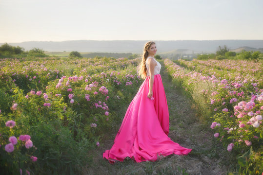 Young woman in spring garden with pink rose flowers, sunset time. She is wearing a beautiful bride dress