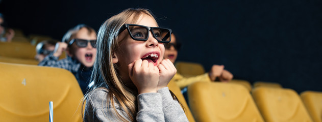 panoramic shot of exited multicultural friends in 3d glasses watching movie together