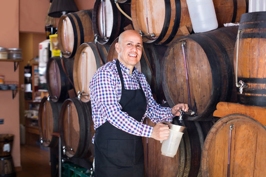 Mature man wine maker taking wine from wood