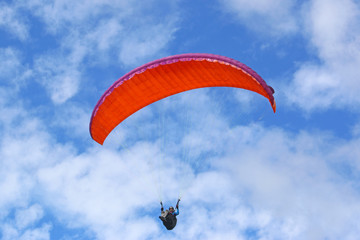 Fototapete - Paraglider flying red wing