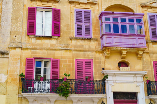 Facade of the house with purple and pink maltese balconies, plants in pots , windows with shutters on yellow limestone townhouse. Typical street scene in ancient city of Mdina, Malta.