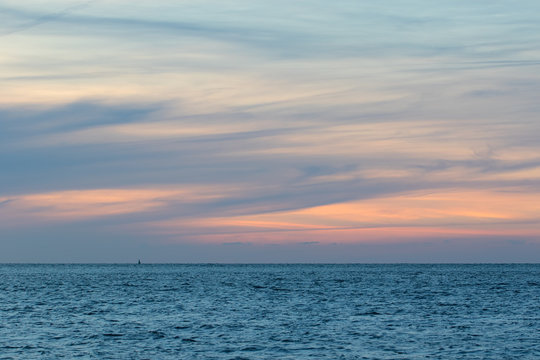 Natural washed pastel cloudscape. Sea and wispy cloud sky at dawn. Soft background image
