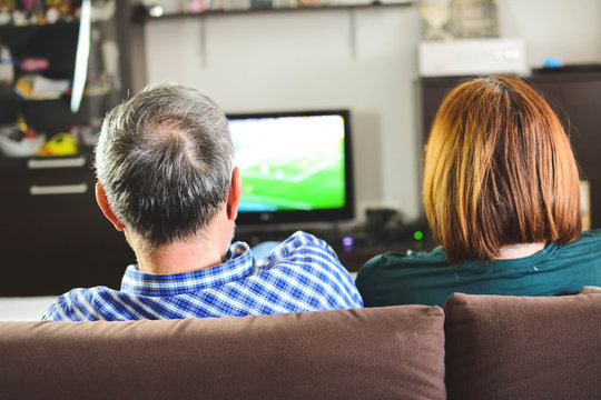 Mature couple watching television.