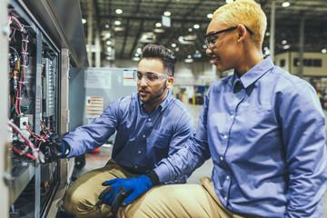 Black service tech inspecting equipment