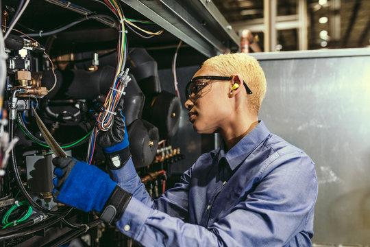 Female service tech inspecting equipment