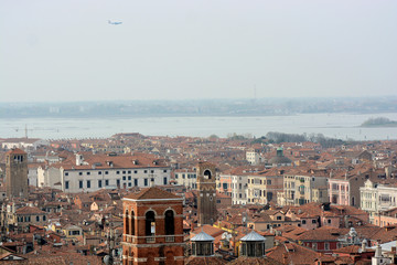 A airplane flies over Venice
