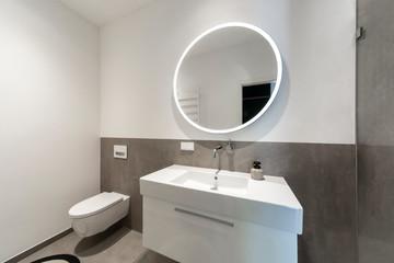 Kleines Modernes Badezimmer mit einem runden Spiegel und großen Fliesen