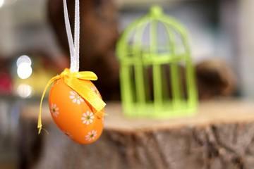 Oeuf de Pâques orange devant une cage miniature