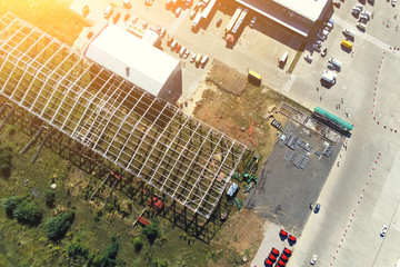 Steel frame construction of modern storage warehouse building at big city suburb. Aerial drone view from above