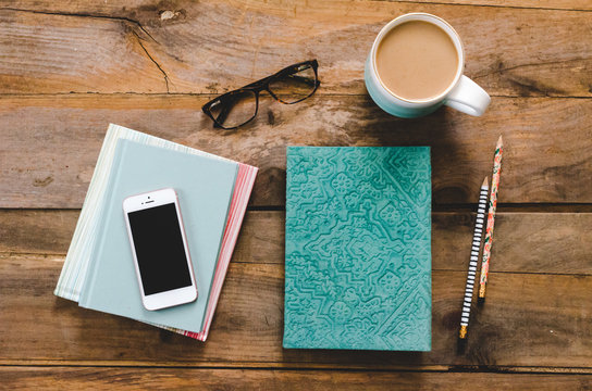 Table scene with glasses, coffee, notebooks, and a smart phone