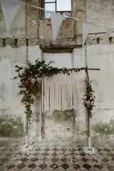 Bohemian handmade macrame backdrop with flowers for wedding ceremony in old abandoned chateau in Normandy
