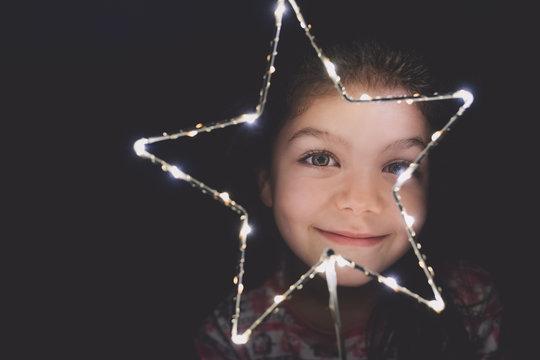 Playful young girl peeking through an illuminated star