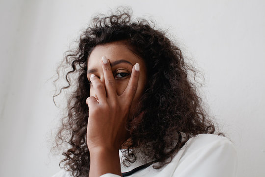 Young woman hiding her face behind her hand