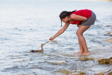 Image of a tween girl in summer shorts feeding a single duck by hand while standing at the edge of the coast.