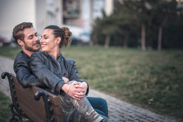 Young sweet couple embraced on a bench in park watching a beautiful sunset, enjoying their love and nature