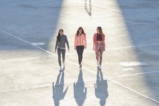 Full length of sportswomen in stylish sportswear walking on stad