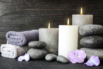 Photo sur Aluminium Spa Composition with zen stones, towels and candles on table against wooden background