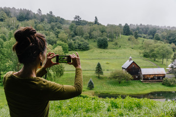 Woman Taking Landscape Photos on her Smartphone