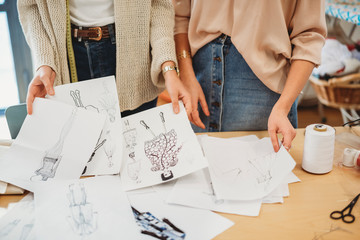 Two young female fashion designers working together at the design studio