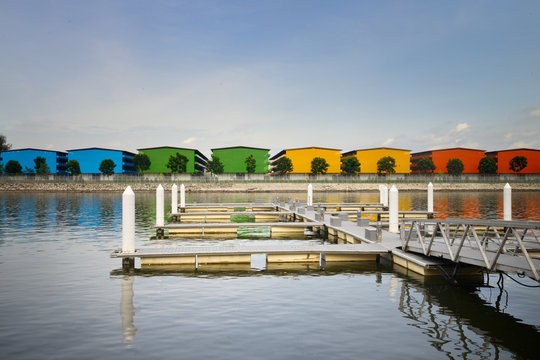 Empty marina with rainbow coloured warehouses in the background on a sunny day