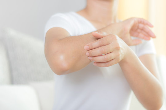 Health care and medical concept. Woman scratching her elbow.