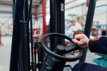 Man driving a forklift truck inside factory