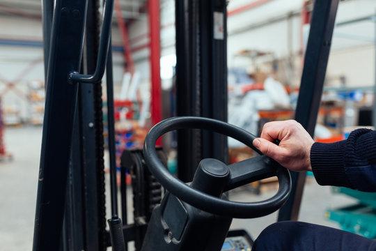 Man driving a forklift truck inside factory
